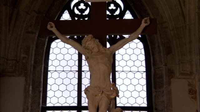 A large crucifix hangs in front of a church window Available in HD.