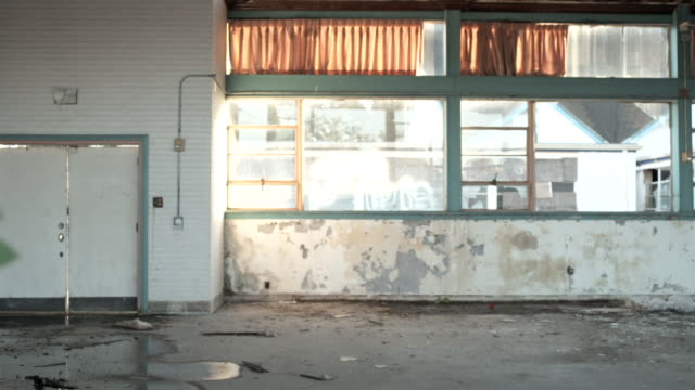Large deteriorating room crumbling plaster paint puddles debris on floor dust dirt graffiti on window Abandoned neglect structure rundown Hurricane...