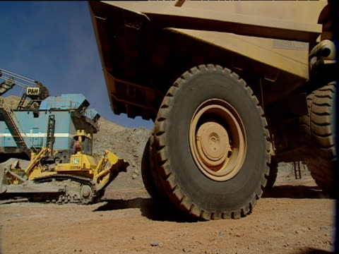Large diamond mines terraced earth trucks and signs