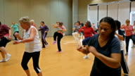 Large diverse group of active seniors in aerobics dance class
