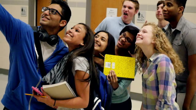 Large diverse group of high school students smiling and posing for selfie photo