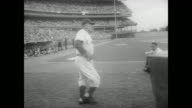Large evening crowd in Shea Stadium / Casey Stengel on the field applauding / crowd stands and begin to applaud / Stengel walks up to large birthday...