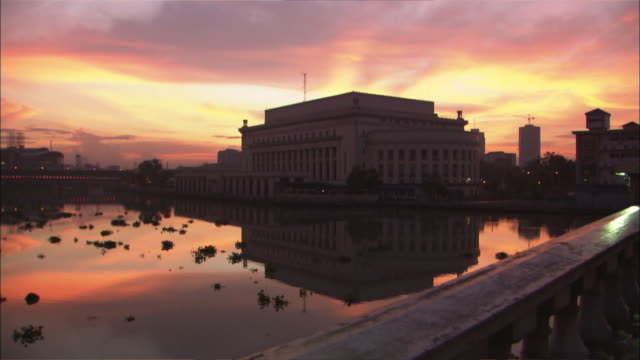 A large government building reflects in water at golden hour.