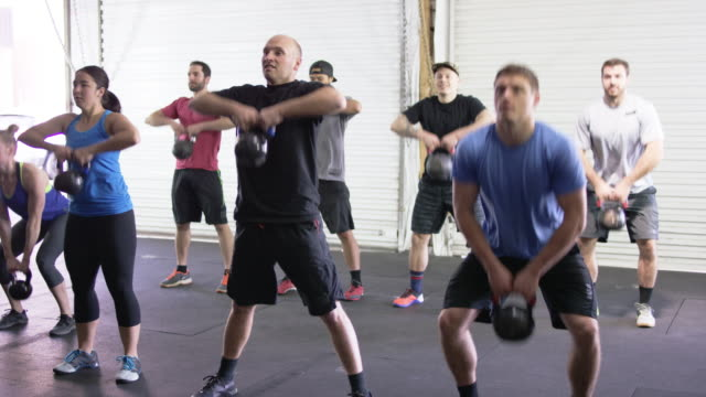Large group class doing a kettlebell workout together in an industrial gym