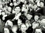 A large group of children smile and wave at the camera