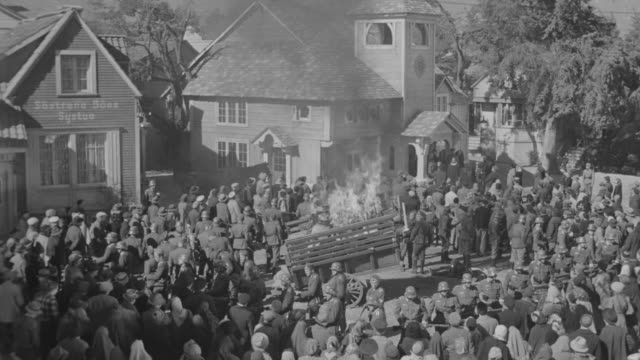 WS HA Large group of Nazis and villagers standing around burring wagon at center of town