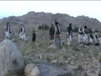 Large group of Taliban forces holding firearms gather on mountainside Afghanistan 2 December 2009