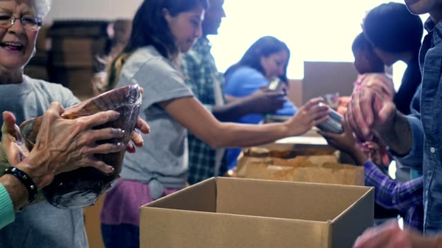 Large group of volunteers pack food in donation boxes