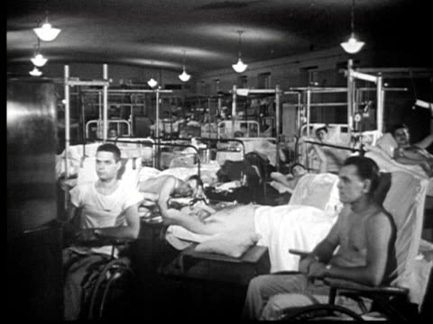 1945 B/W MONTAGE Large hospital ward w/ injured men watching small television / USA / AUDIO