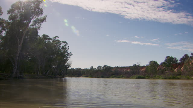 A large houseboat travels along the Murray River in Australia.