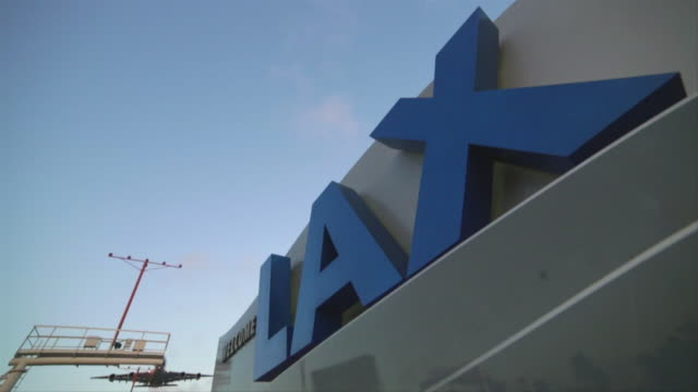 Large Jumbo Jet Landing over LAX welcome sign