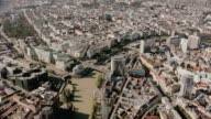 AERIAL Large muddy river dividing one half of densely populated city from the other