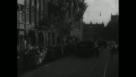 A large open Nazi car comes to a stop and an official steps out and proceeds to building interior hall with huge eagle flanked by swastikas / tall...