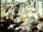 1960 MONTAGE Large outdoor feast on ground. Men eating with hands wearing flowing white robes and ornate turban hats. CU dishes of food Some with rifles and bullet belts / Peshwar, Pakistan