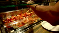 Large pan bin of king crab legs on restaurant buffet line unidentifiable workers behind counter moving about unidentifiable customer hands w/ tongs...