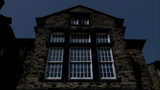 A large pane of windows covers one side of a stone building. Available in HD.