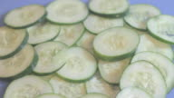 Large pile of cucumber slices sitting on a blue cutting board, side raised view.