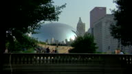 WS Large rounded reflective surface of 'Cloud Gate' sculpture reflecting skyline people low wall trees FG skyscrapers BG ZI CU Reflections City urban...