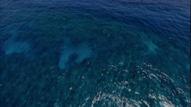 A large sandbar breaks the surface over the Great Barrier Reef. Available in HD.
