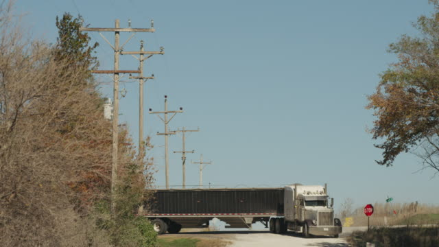 Large semi truck and trailer loaded with grain, turns onto a rural gravel road lined with telephone poles.