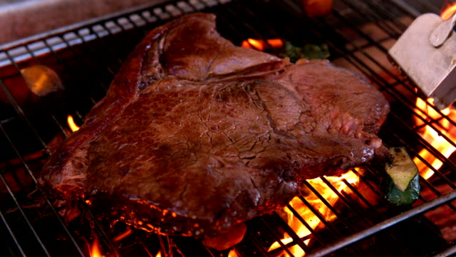 Large steak being cooked on flaming barbecue