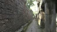 A large stone wall shades a colonnade at the Bayon temple in Angkor, Cambodia.