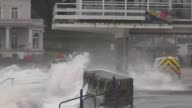 Large storm waves breach the sea wall at Paignton Devon UK causing flooding and damage Emergency vehicle drives through with waves breaking