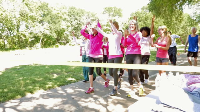 Large team of women crossing finish line during breast cancer awareness race for charity