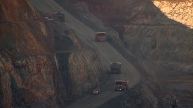 large trucks carry rocks from the Kalgoorlie Super Pit in Western Australia.