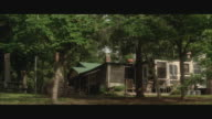 WS Large two story wooden house surrounded by trees