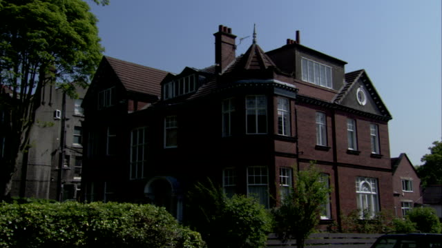 A large Victorian red brick home features a corner tower. Available in HD.