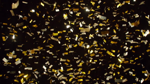 SLO MO A large volume of gold sequins falling and sparkling