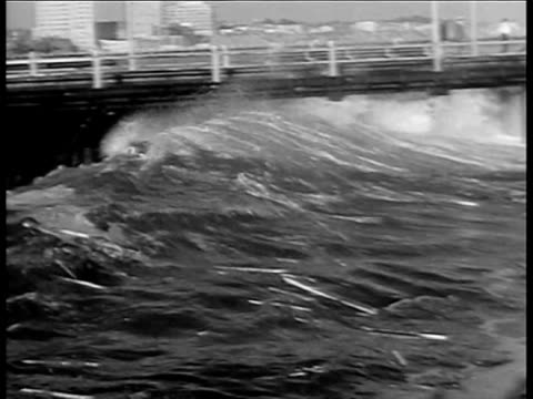 Large wave from storm sweeping below pier carrying debris / wave crashing over rocks onto land / surf spray over rocks under pier Spectacular storm...