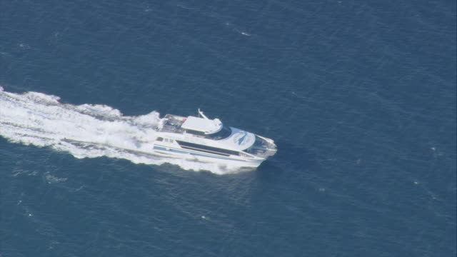 AERIAL Large yacht steaming past Elizabeth Islands, wake stretching far back / Massachusetts, United States