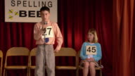 Last two finalists sitting on stage in spelling bee / boy walking up to microphone / zoom in to boy spelling word / Los Angeles, California