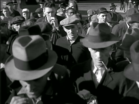 B/W late 1920s close up men in hats walking slowly past camera to enter factory