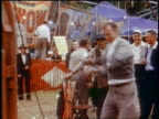Late 1950s man lifting hammer above head in Test Your Strength game at carnival / newsreel