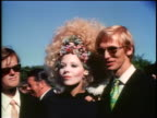 Late 1960s PORTRAIT 2 young Scandinavian men + woman with big frizzy hair standing at outdoor event
