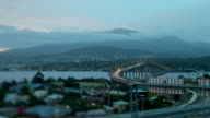 Late afternoon day to night timelapse Tasman Bridge and Hobart Looking across Tasman Bridge and Derwent River towards cloud obscured Mount Wellington...