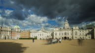 Late afternoon sunlight lights the facade of Horse Guards Palace as dark clouds pass overhead as tourists visiting Horse Guards Parade move rapidly through the frame