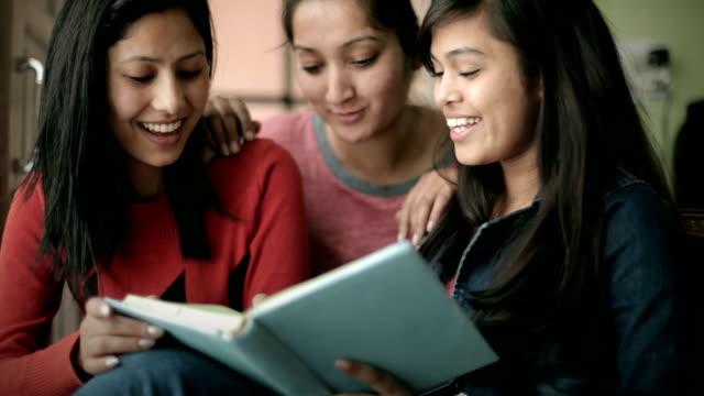 Sen tonåring glad tjej studenter som läser en bok tillsammans.