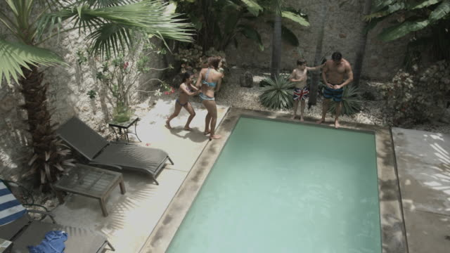 Latin Family playing in Pool of Holiday Home