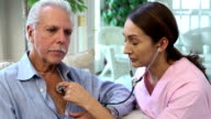 Latin Healthcare Professional Listens to Heart of Senior Man