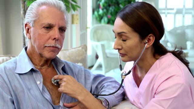 Latin Healthcare Professional Listens to Heart of Senior Man