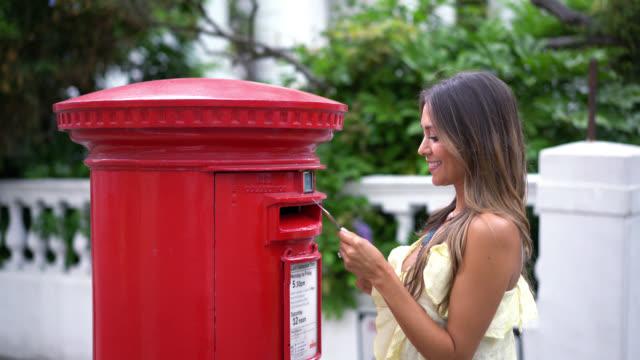 Latijnse vrouw zetten een brief in een traditionele brievenbus in Londen
