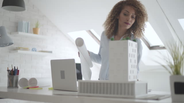 Latina Architect Working In Her Office.