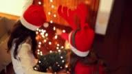 Latino Lifestyle. Girls removing knots of Christmas lights.