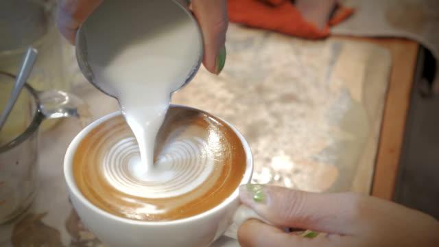 Latte art, von einem Barista gießen Milch
