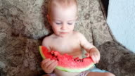 Laughing child eating watermelon