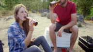 MS Laughing couple drinking beer and petting dog at campsite